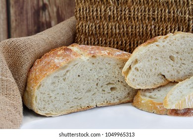 Fresh baked sliced loaf of artisan bread in front of wicker and burlap.  Macro