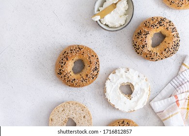Fresh baked sourdough New York style bagels with philadelphia cheese on light table, top view
