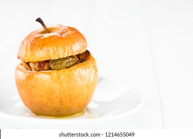 Fresh baked stuffed apple with walnut, almond, raisin, sultana, butter, sugar, cinnamon, traditional autumn and winter dessert, copy space on the right side (Selective Focus on the front of the apple)