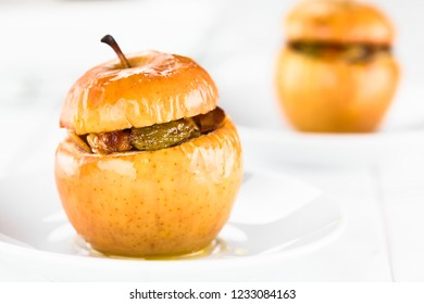 Fresh baked stuffed apple with walnut, almond, raisin, sultana, butter, sugar, cinnamon, traditional autumn and winter dessert, photographed on white wood (Selective Focus on front of the left apple)