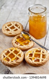 Fresh baked tarts with marmalade filling and apricot jam in glass jar on cutting board on rustic wooden table background.