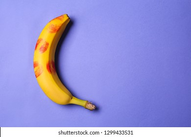 Fresh banana with lipstick prints on color background. Erotic concept