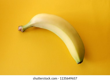 Fresh banana on a bright yellow colored background texture