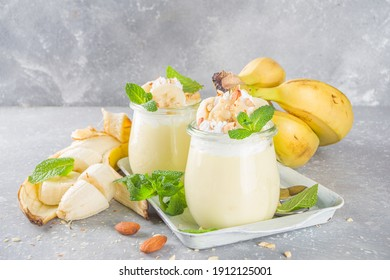 Fresh banana pudding for breakfast, banana yogurt. Sweet dessert in glasses with banana slices and nuts, raw vegetarian snack, on grey concrete background with fresh yellow bananas