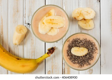 Fresh banana smoothie with chia seeds on an old white table