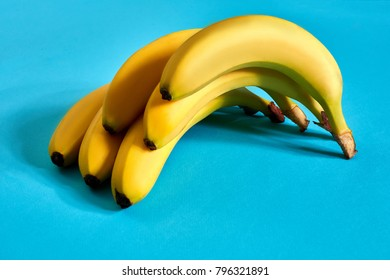 Fresh bananas close up on bright blue background. Flat lay. Summer concept.