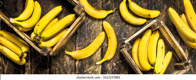 Fresh bananas in old boxes. On a wooden background.