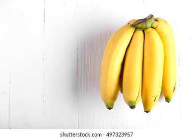 Fresh bananas on wooden background.