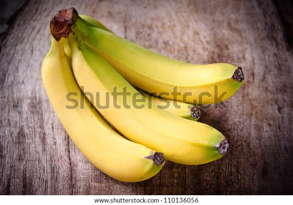 Fresh bananas on wooden background