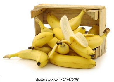 fresh bananas and a peeled one in a wooden crate on a white background