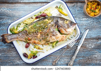 Fresh barbecue gilthead seabream with mango chutney and pesto as top view in a white skillet