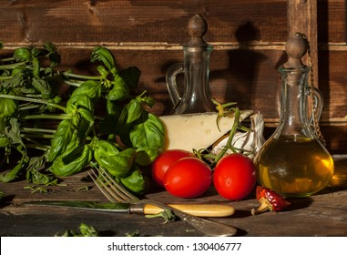 fresh basil, garlic, wet red cherry tomatoes and cheese parmesan on wooden table with olive oil in vintage glass bottle
