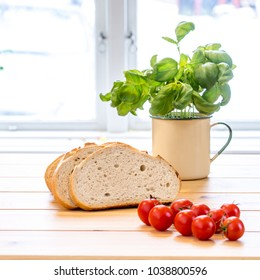 fresh basil, tomatoes and sliced bread o the kitchen table