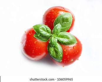 fresh basil and tomatoes with water drops on white backgrounds