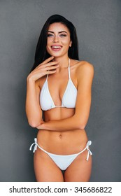 Fresh and beautiful. Attractive young smiling woman in white bikini posing against grey background