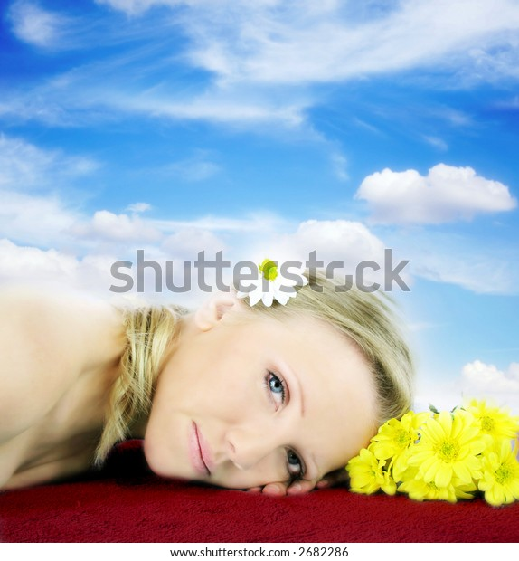 a fresh and beautiful blond woman laying on a red towel with flowers in front of the blue sky with clouds
