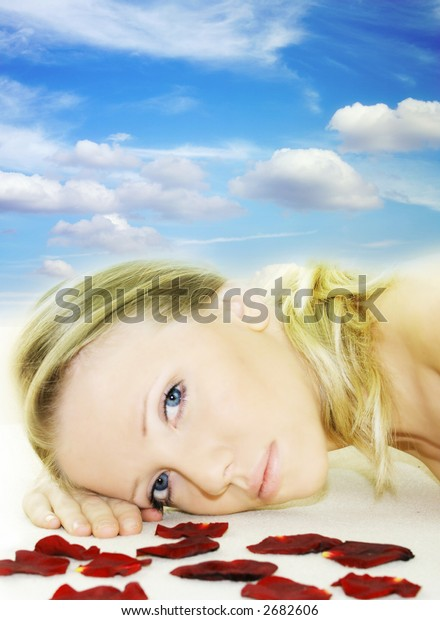 a fresh and beautiful blond woman laying on a yellow towel with flowers and in front of the blue sky