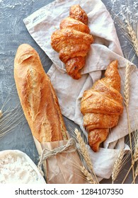 Fresh beautiful bread and croissants with gray textile, baking flour and spikelets of wheat on a gray background