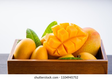 Fresh and beautiful mango fruit set in a wooden box with sliced diced mango chunks isolated on a white background, copy space(text space), blank for text