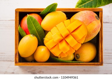 Fresh and beautiful mango fruit set in a wooden box with sliced diced mango chunks on a light wooden background, copy space(text space), blank for text, topview, copyspace, closeup