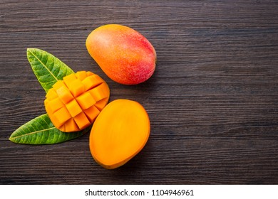 Fresh and beautiful mango fruit with sliced diced mango chunks on a dark wooden background, copy space(text space), blank for text, top view.