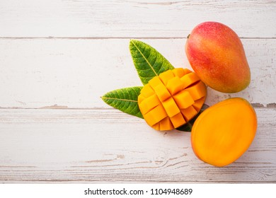 Fresh and beautiful mango fruit with sliced diced mango chunks on a light wooden background, copy space(text space), blank for text, topview.