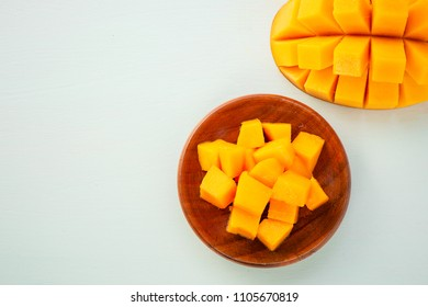 Fresh and beautiful mango fruit with sliced diced mango chunks on a light blue background, copy space(text space), blank for text, top view, topview, copyspace, closeup