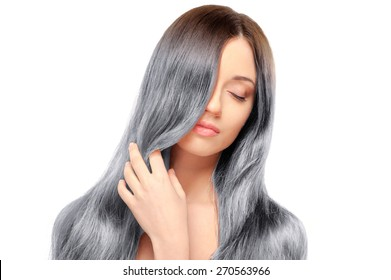 Fresh and beautiful. Portrait of beautiful young woman with closed eyes and holding hand on her long gray hair while standing against white background