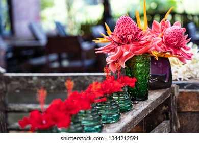 Fresh and beautiful red flowers with soft focus and bokeh, there are showed in clear green color vase on wooden porch