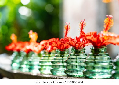 Fresh and beautiful red petal with soft focus and bokeh , there are showed in clear green color vase on wooden porch