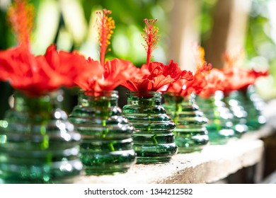 Fresh and beautiful red petal with soft focus , there are showed in clear green color vase on wooden porch