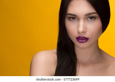 Fresh beauty. Close up studio shot of a beautiful young seductive brunette wearing violet lipstick and golden eyeliner on yellow background copyspace beauty creative makeup model colorful visage lips