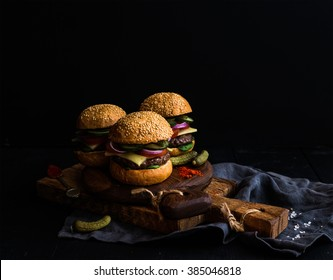 Fresh beef burgers with pickles and spices on rustic wooden boards, black background. Selective focus, copy space