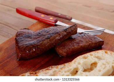 fresh beef meat steak with red hot pepper and bun slices served on plate with whiskey on wood over table with cutlery