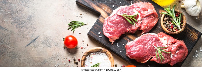 Fresh beef steak with herbs on stone table. Top view.