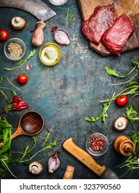 Fresh beef steak, wooden spoon, knife and aromatic herbs, spices and vegetables for cooking , on rustic background, top view, frame.