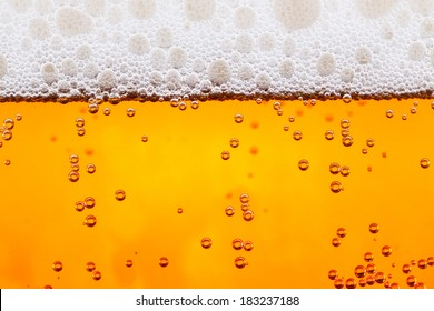 fresh beer with bubbles close up background