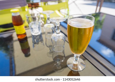 Fresh beer and empty glasses on  an outdoor glass table in a restaurant