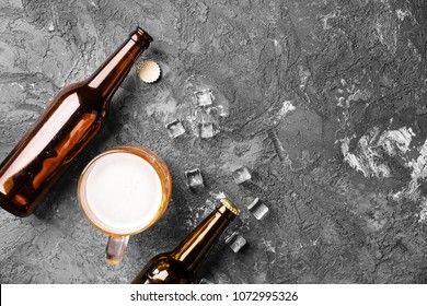 Fresh beer in glass bottles and mug on gray background