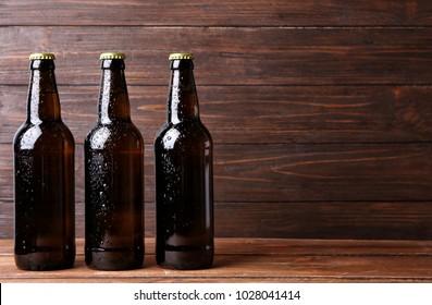 Fresh beer in glass bottles on wooden background