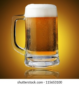 Fresh beer in glass with foam on yellow background