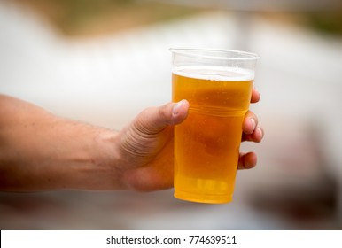 Fresh beer in a plastic cup in the hand