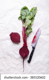 fresh beetroot with green leaves from farmer's market, cut in half, isolated on a wrinkled white paper background with a bloody knife, top view, vertical