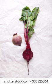 fresh beetroot with green leaves from farmer's market, cut in half, isolated on a wrinkled white paper background, top view, vertical