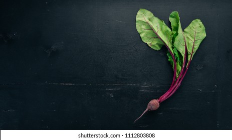Fresh beetroot with green leaves. On a wooden background. Top view. Copy space.