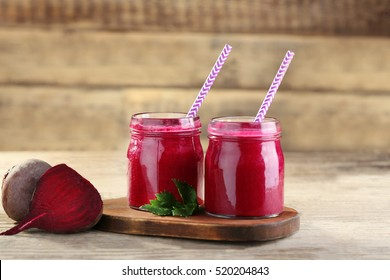 Fresh beetroot smoothie and vegetables on wooden wall background