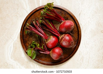 Fresh beetroots on metal tray on marble table