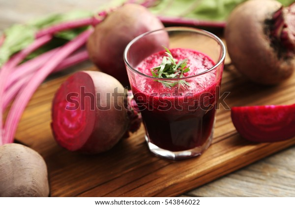 Fresh beets juice in glass on a grey wooden table
