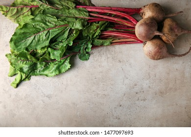 Fresh beets with leaves on grey table, top view. Space for text