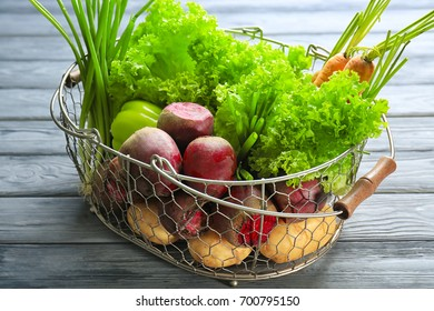 Fresh beets with vegetables in metal basket on table